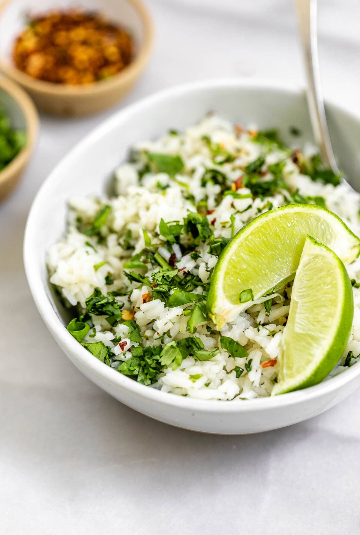 Angled view of the rice with chopped cilantro and lime wedges.