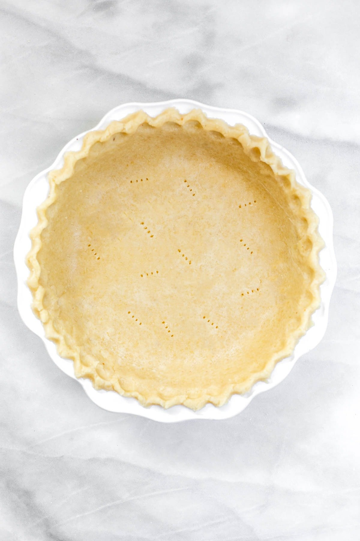 Final gluten free pie crust in a white plate.