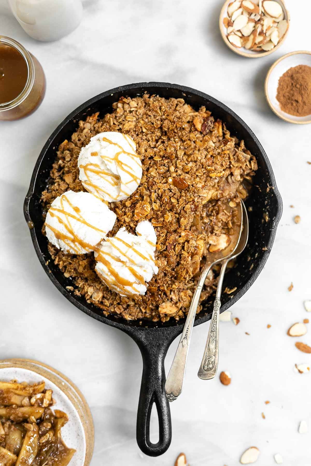 Apple crisp in a cast iron skillet with three scoops of ice cream.