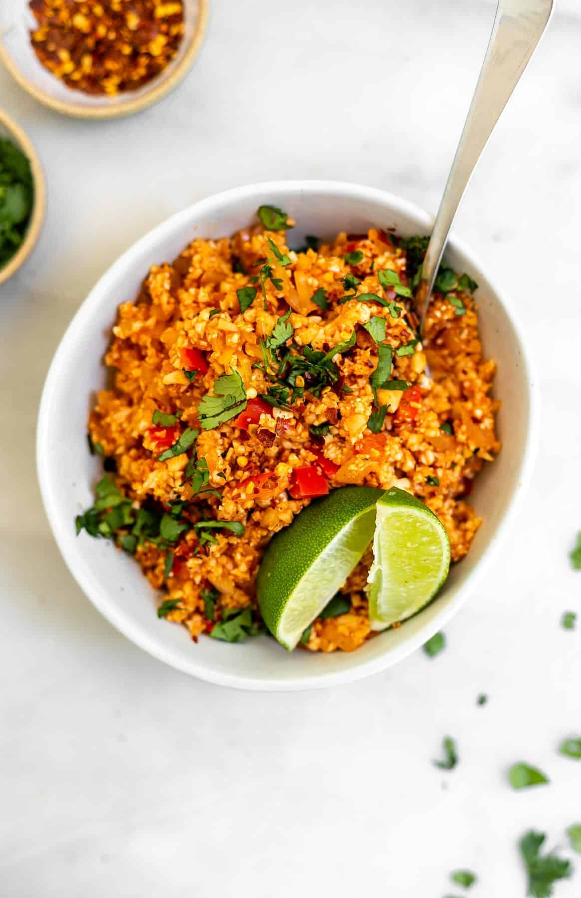 Mexican cauliflower rice in a bowl with red pepper flakes on the side.