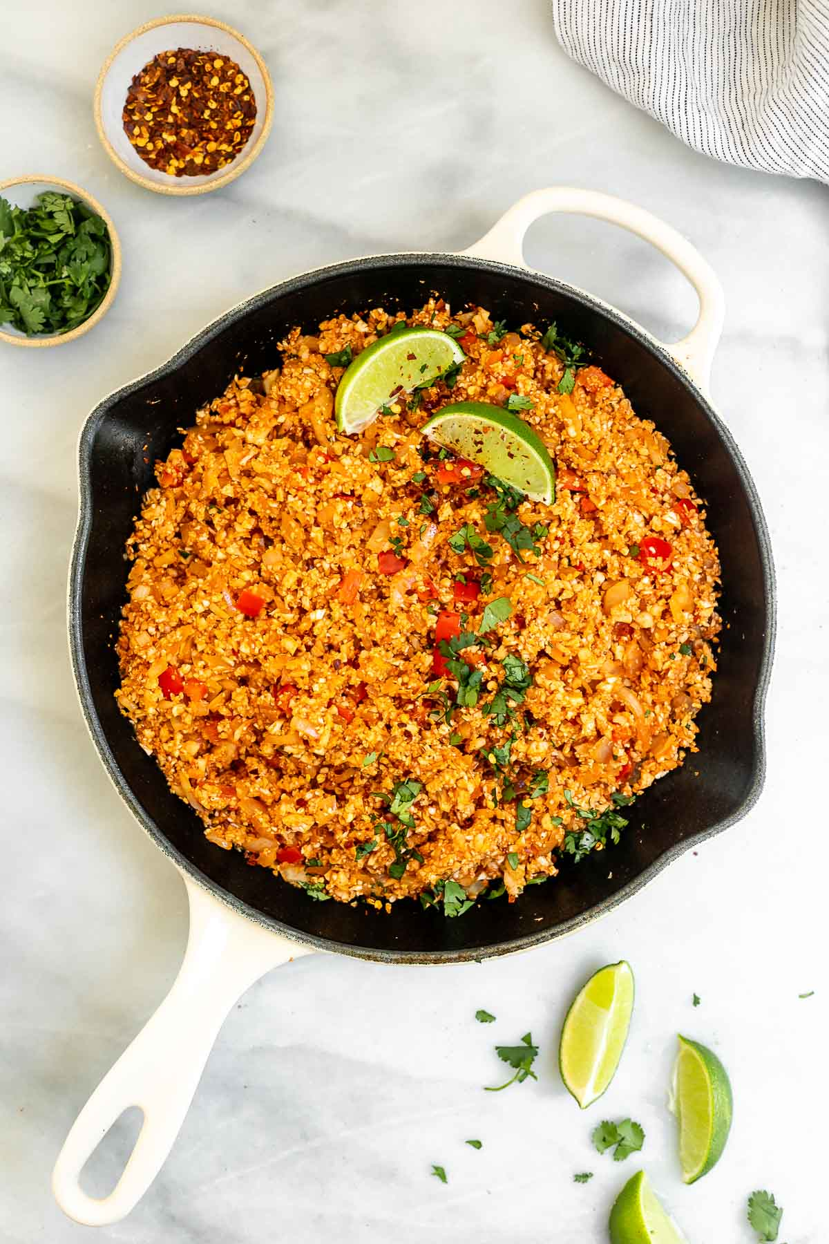 Mexican cauliflower rice in a pot with lime wedges.