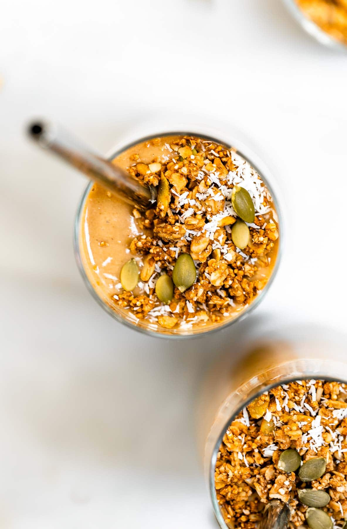Smoothie with pumpkin seeds on top with a straw.