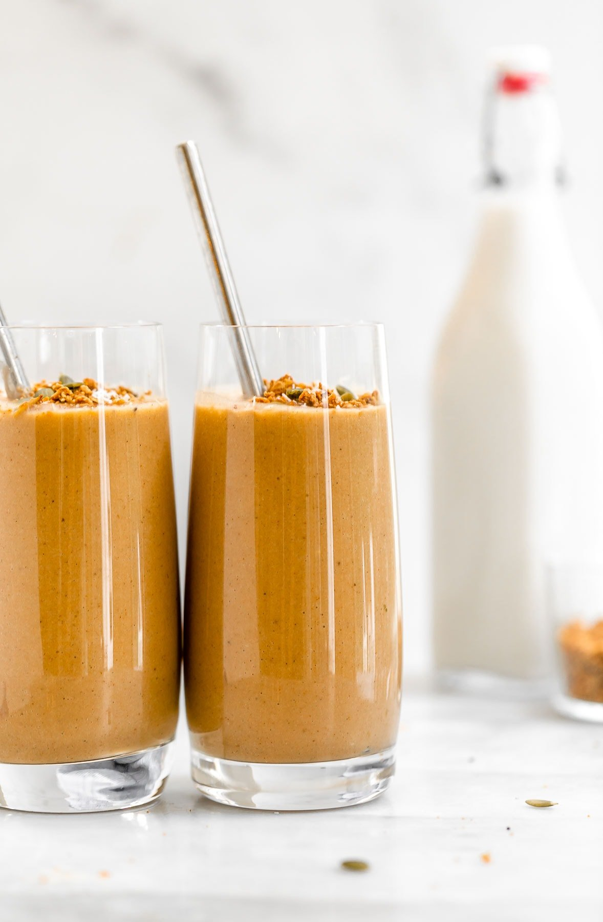 Two sweet potato smoothies with milk in the background.