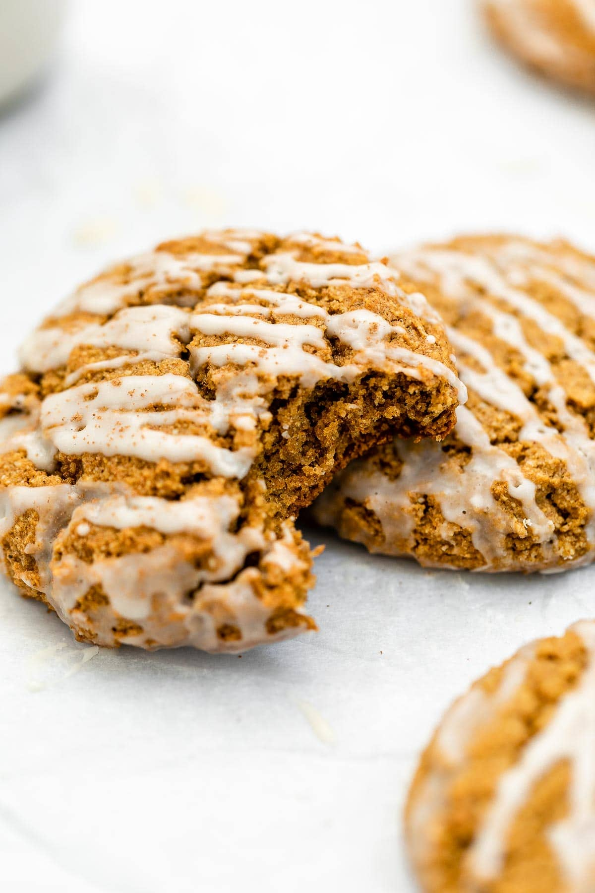 Two vegan pumpkin cookies on the side with a bite taken out.