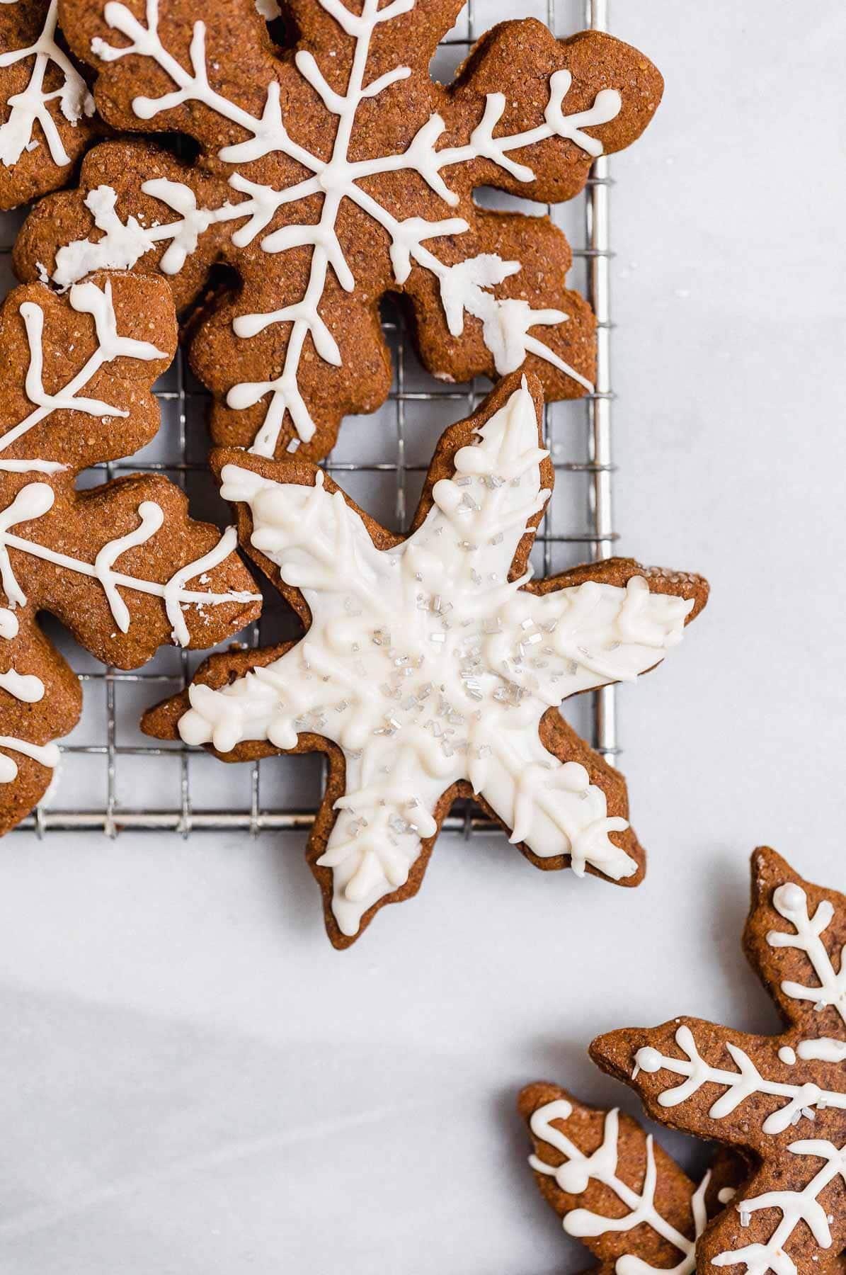 Vegan snowflake gingerbread cookies with icing and sprinkles.