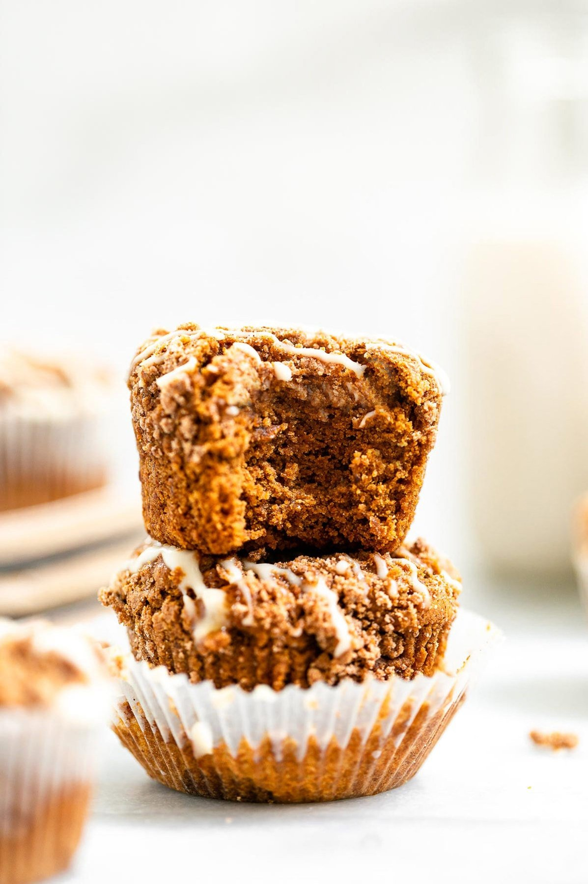 Two muffins stacked on each other with a bite taken out.