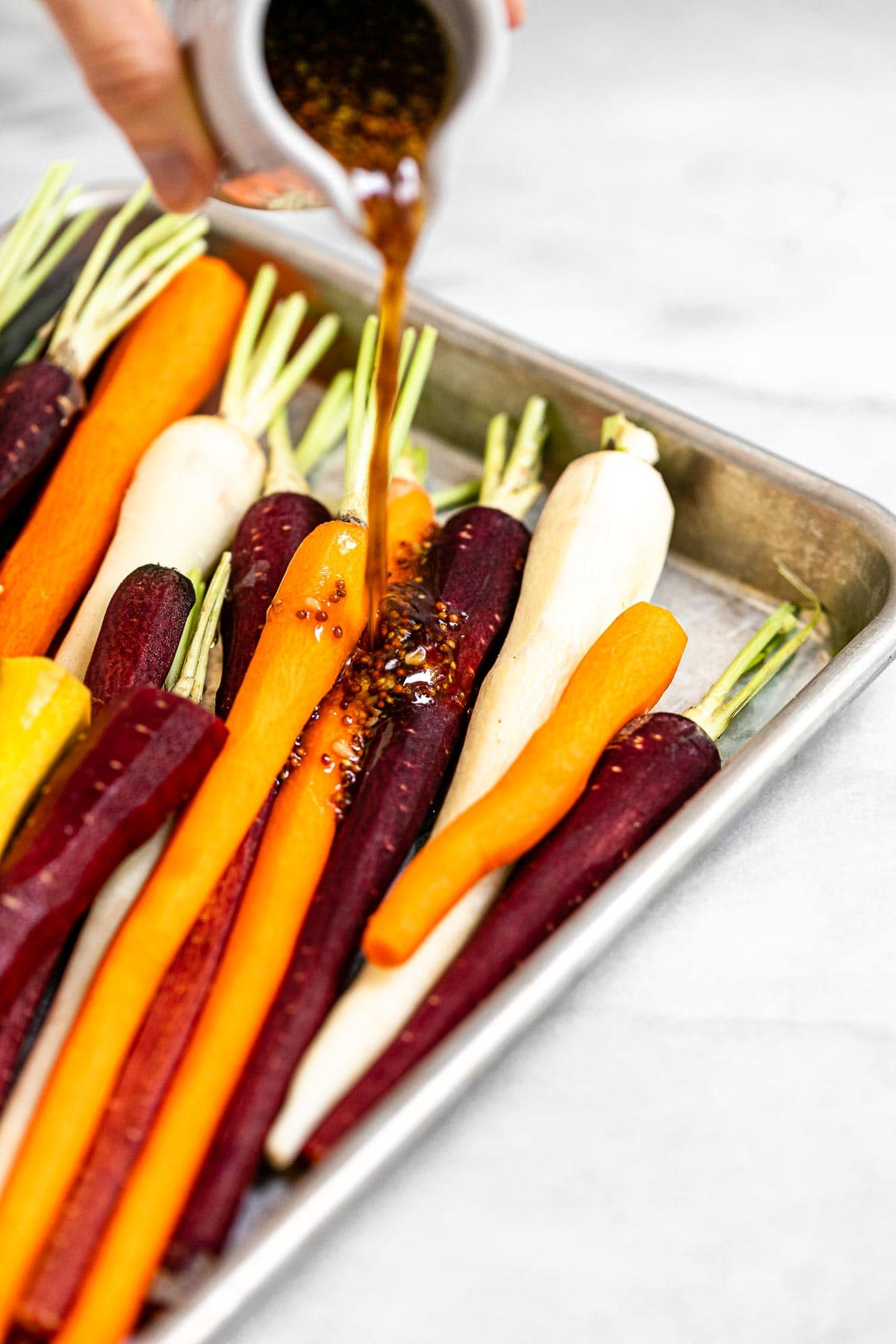 Pouring the sauce over the carrots.