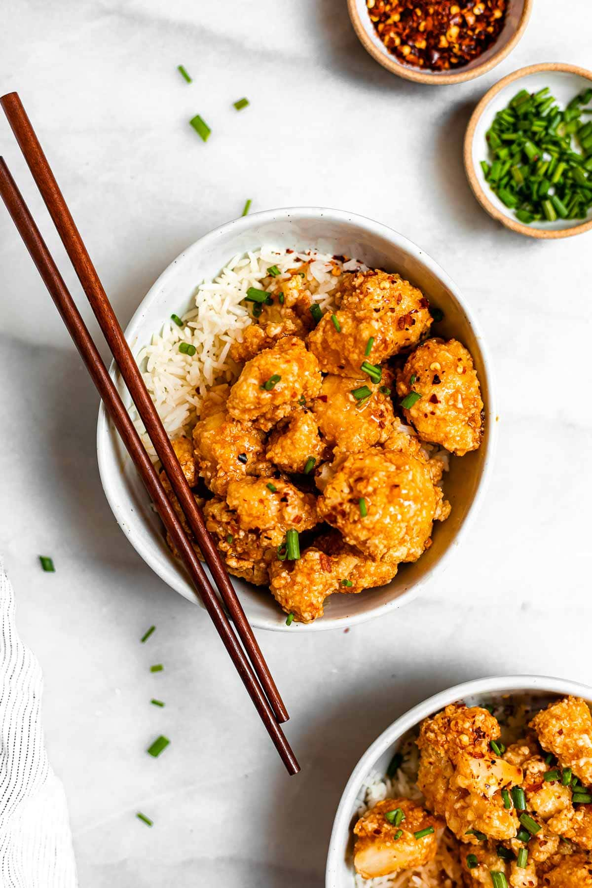 Final orange cauliflower in a bowl with rice and chopsticks.