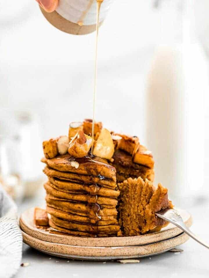 Tall stack of sweet potato pancakes with a bite taken out.