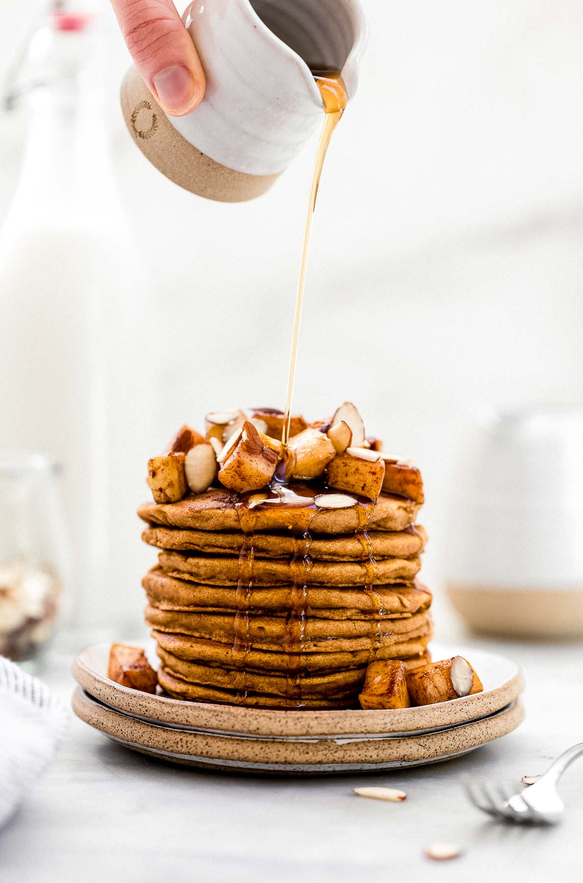 Tall stack of vegan sweet potato pancakes with apples on top.