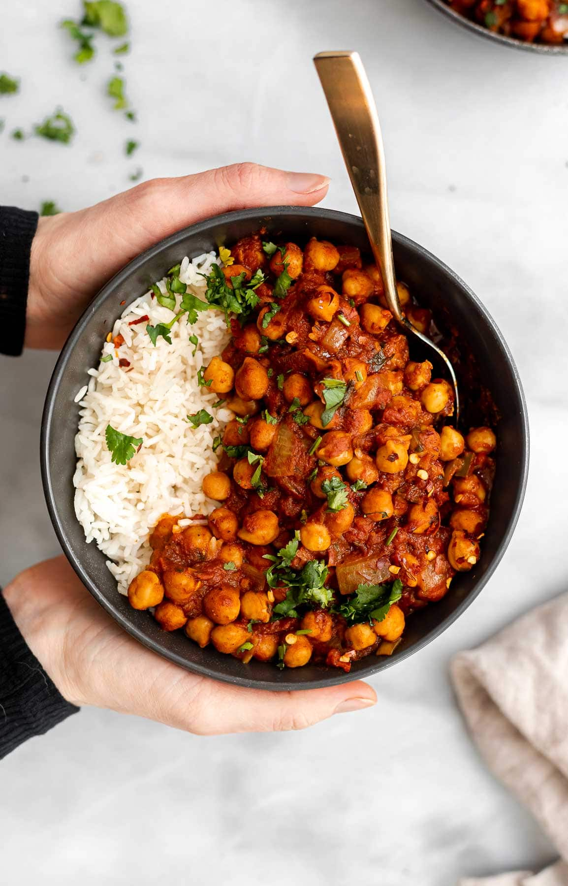 Hands holding a bowl of the vegan chana masala with white rice.