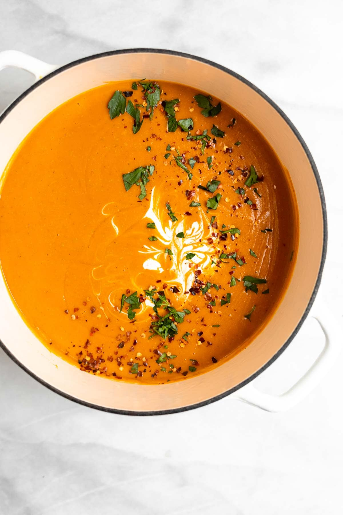 Red lentil and carrot soup in a large white pot.