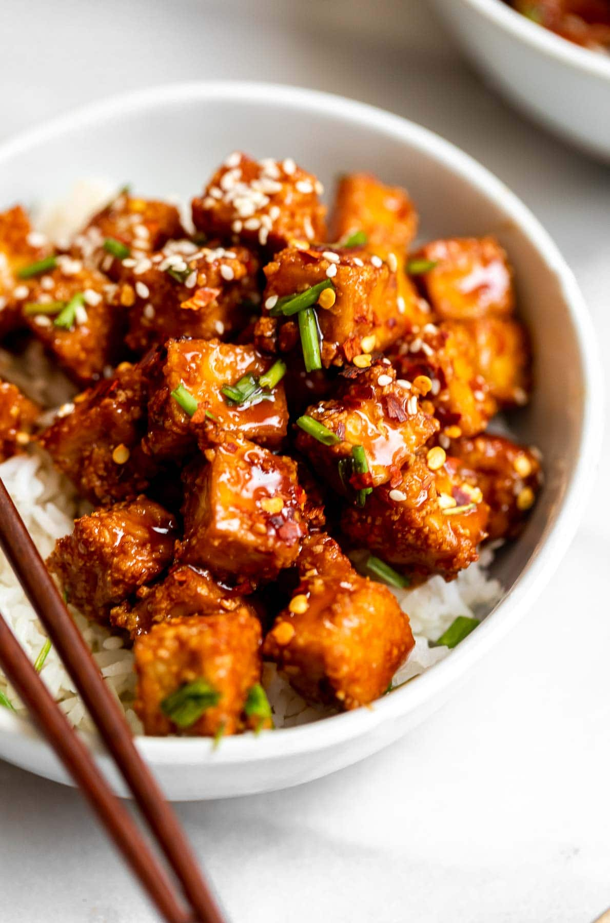 Baked teriyaki tofu with chopped chives on top in a bowl.