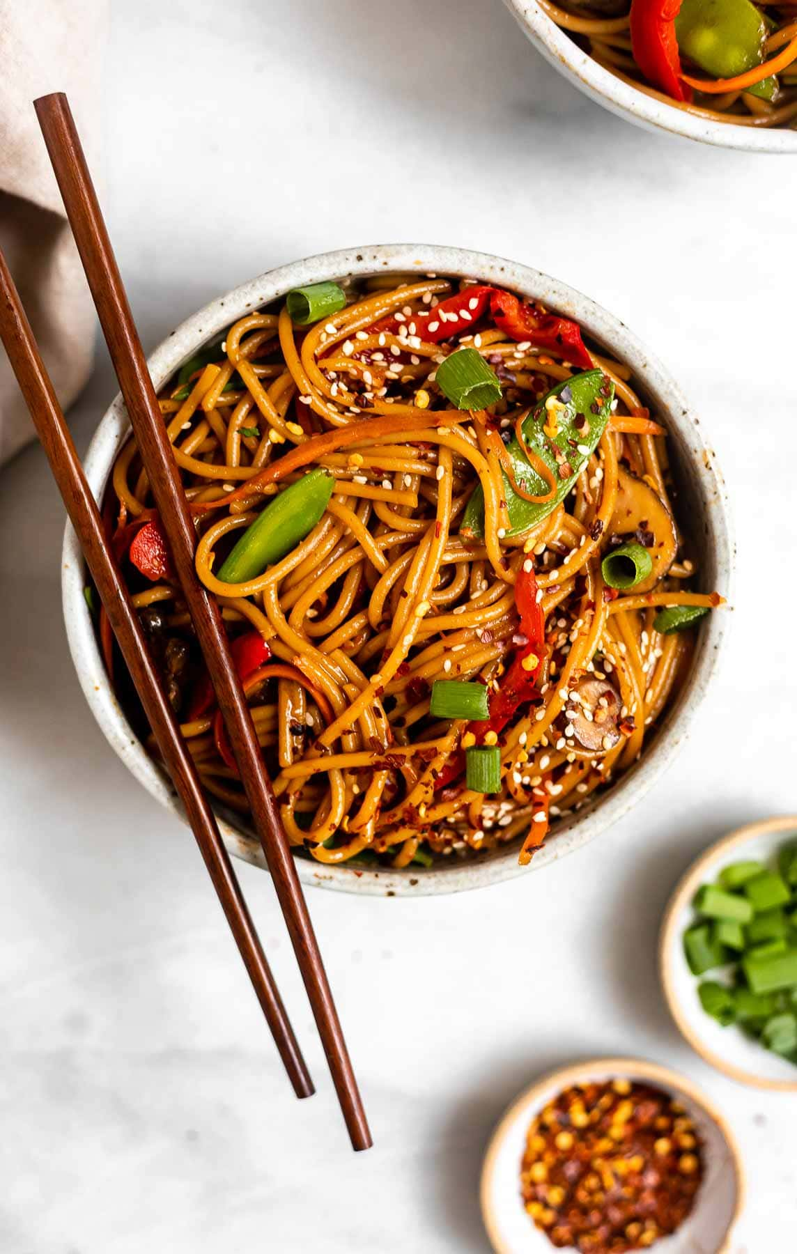 Vegetable lo mein with chopsticks on the side of the bowl.