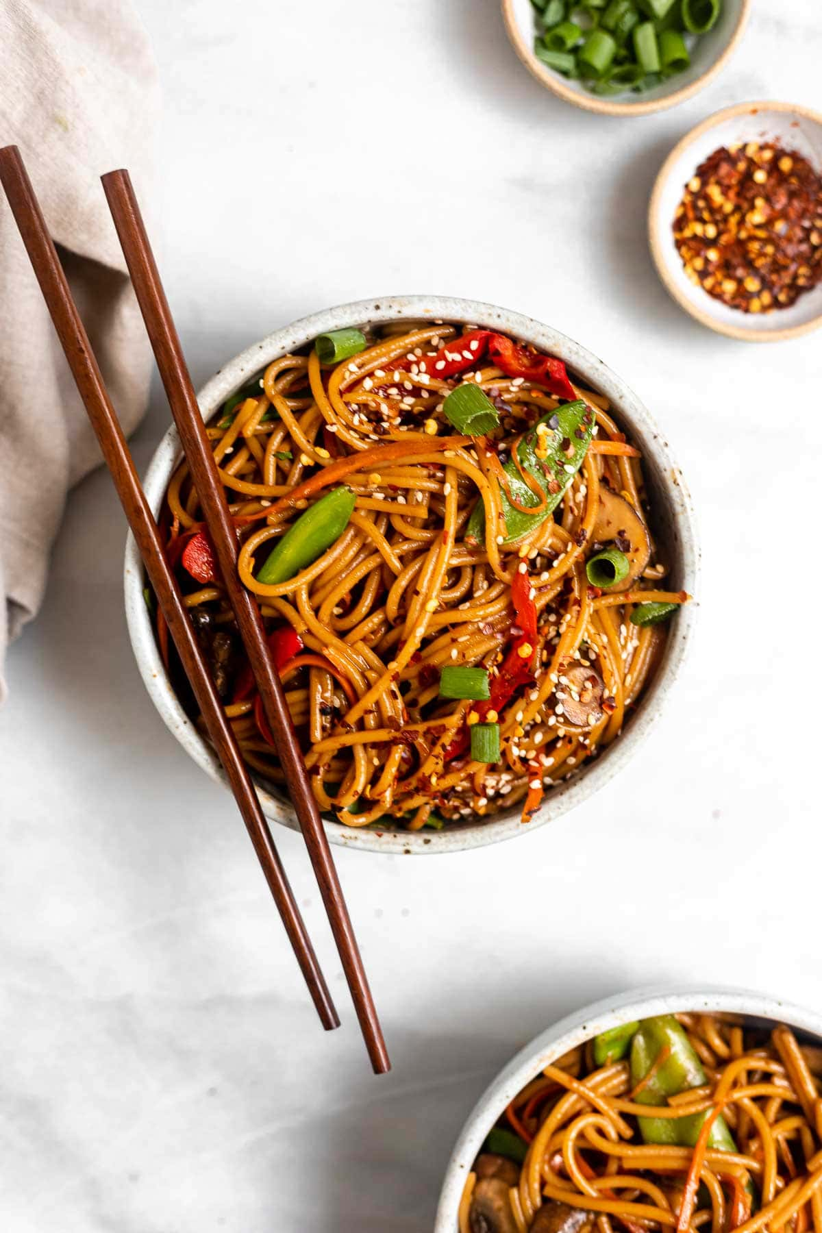 Two bowls of the vegetable lo mein with sesame seeds on top.
