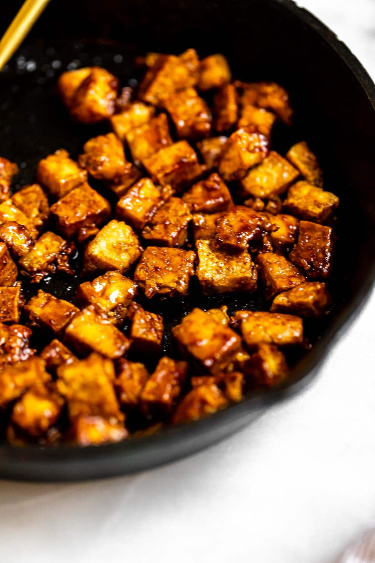 Pan fried tofu in a pan with soy sauce on top.