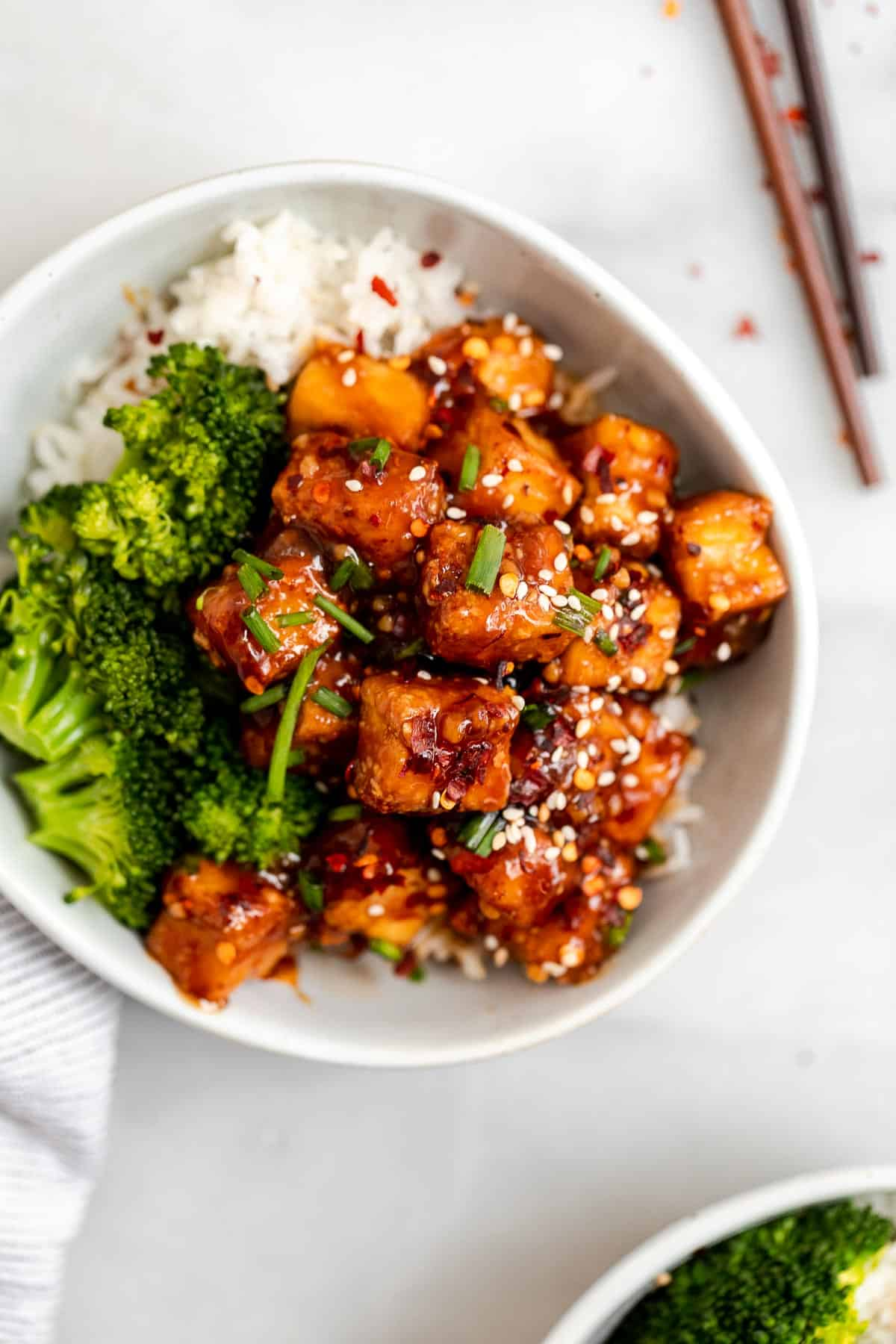 up close image of the air fried tofu in a bowl with broccoli