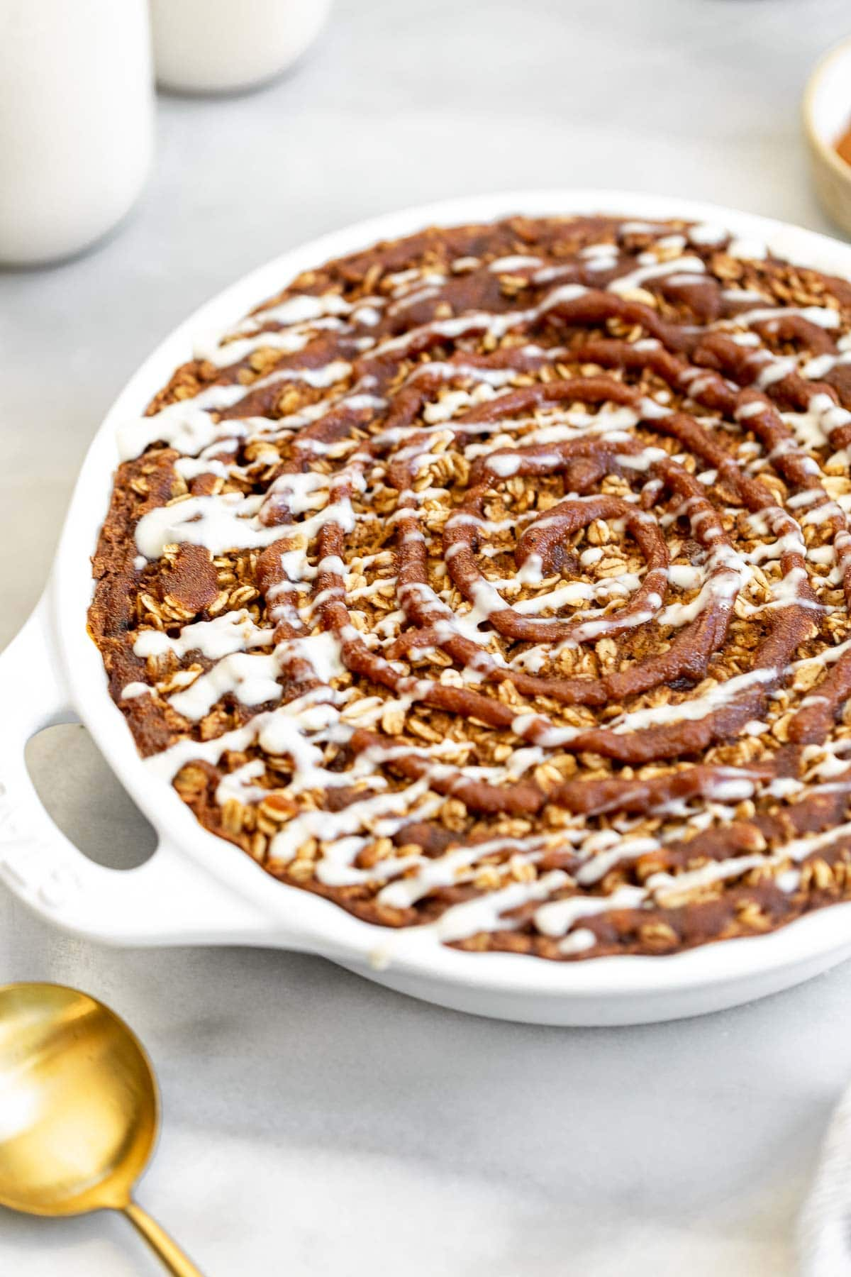 cinnamon roll baked oatmeal in a pie dish with icing