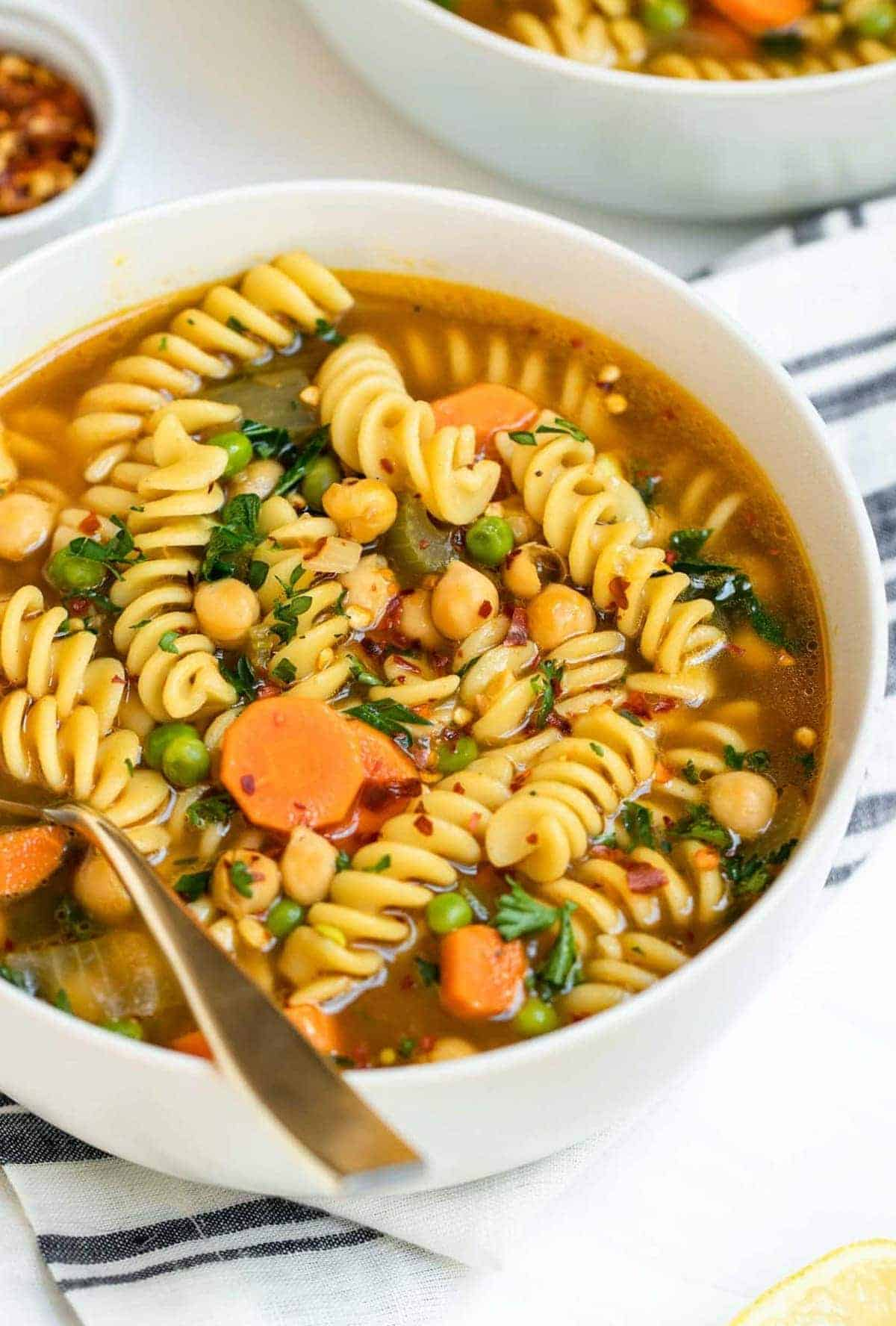 up close of the chickpea noodle soup with a spoon on the side