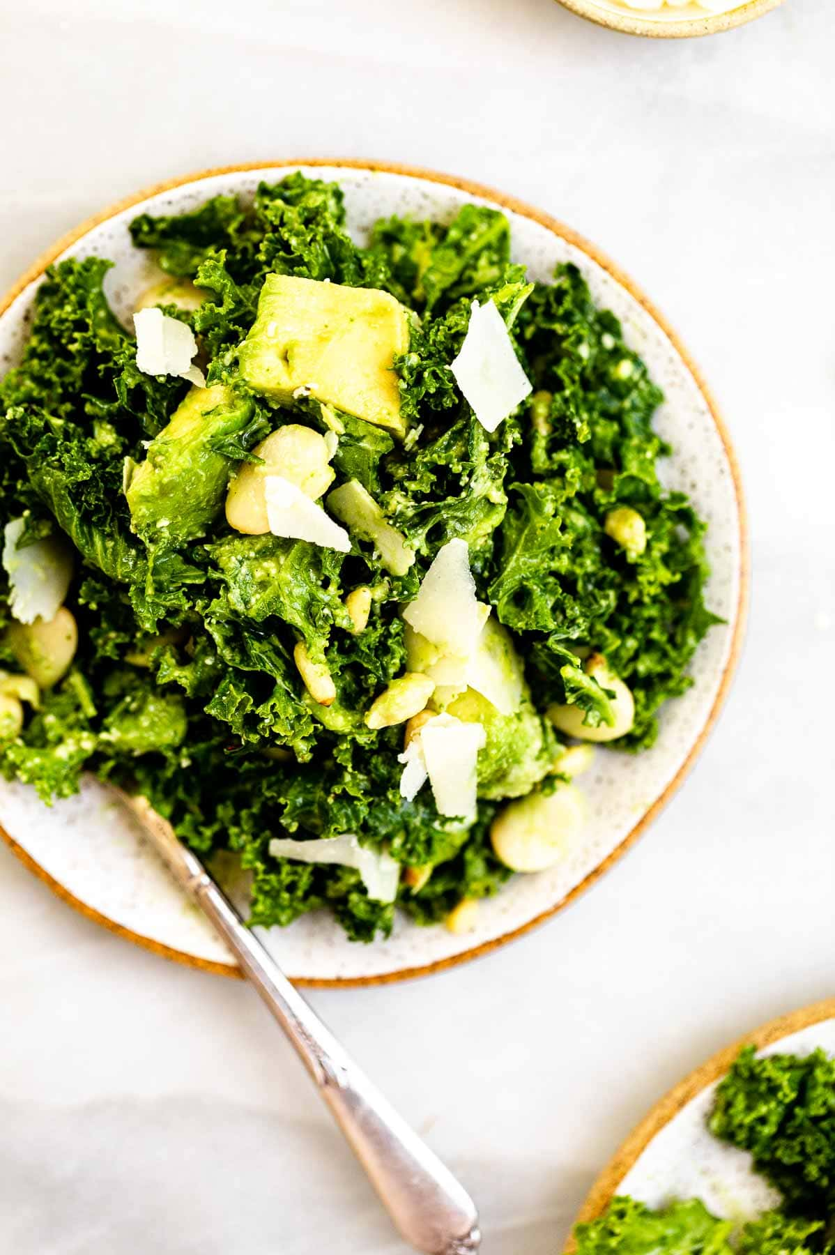 Kale avocado salad on two plates with a fork on the side.