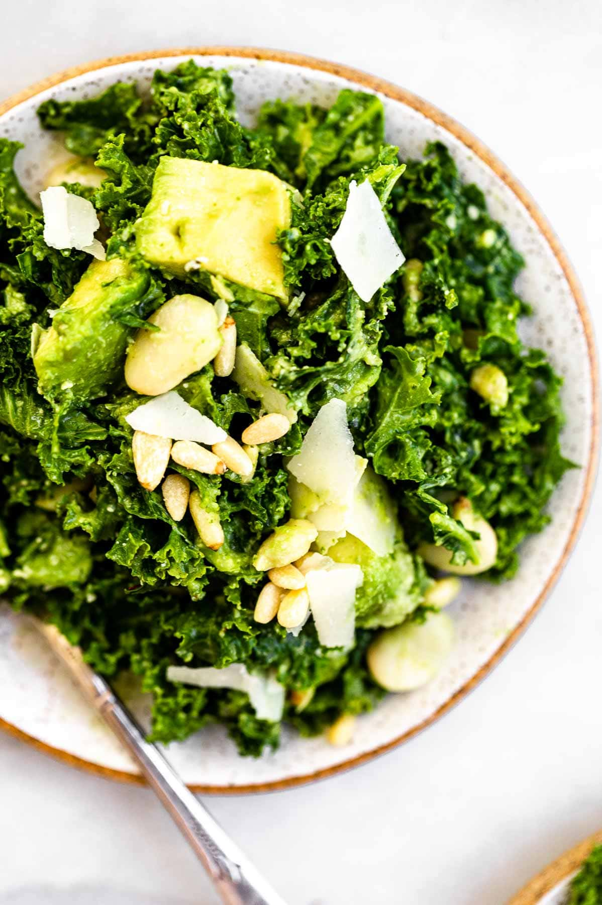 Massage kale avocado salad with pine nuts and parmesan.