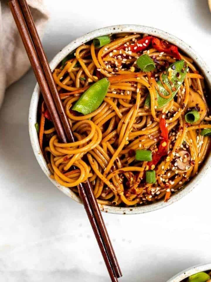 Vegetable lo mein in a pot with chopsticks running through the noodles.