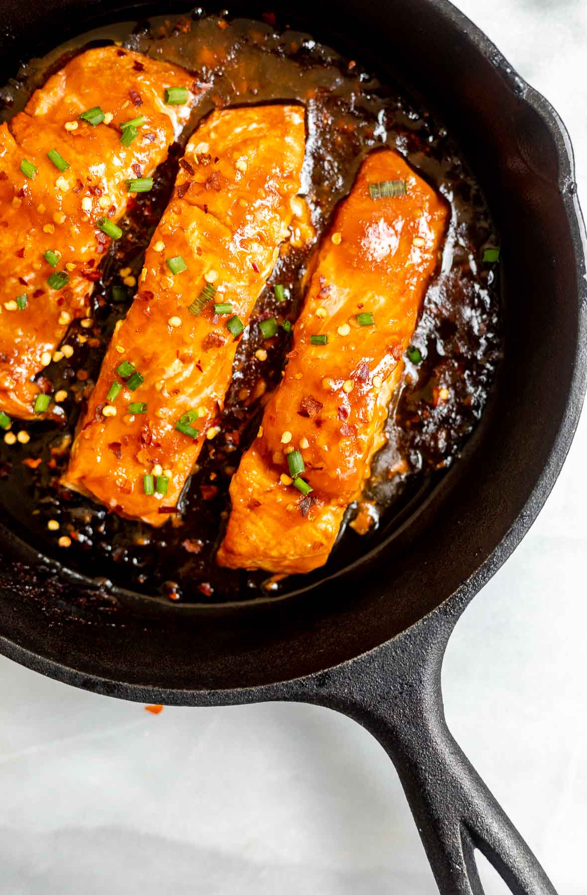 Pan fried orange salmon with chives on top in a skillet.
