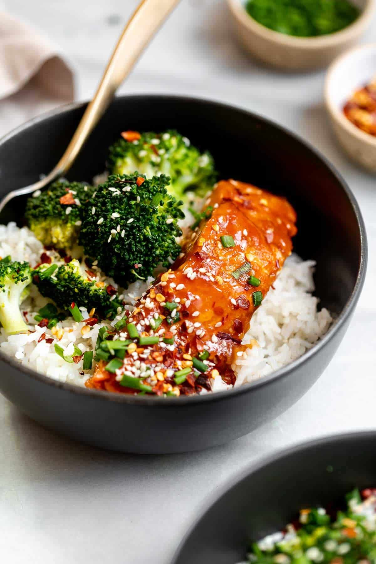 Orange salmon in a dark bowl with rice and broccoli.