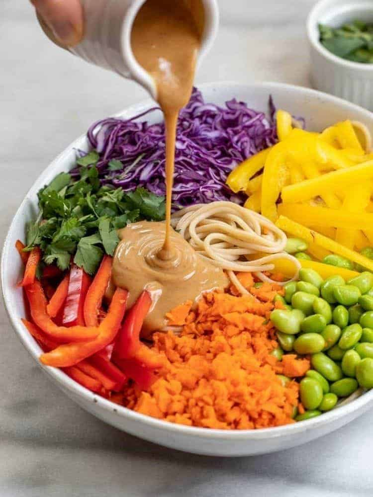 pouring peanut sauce over salad