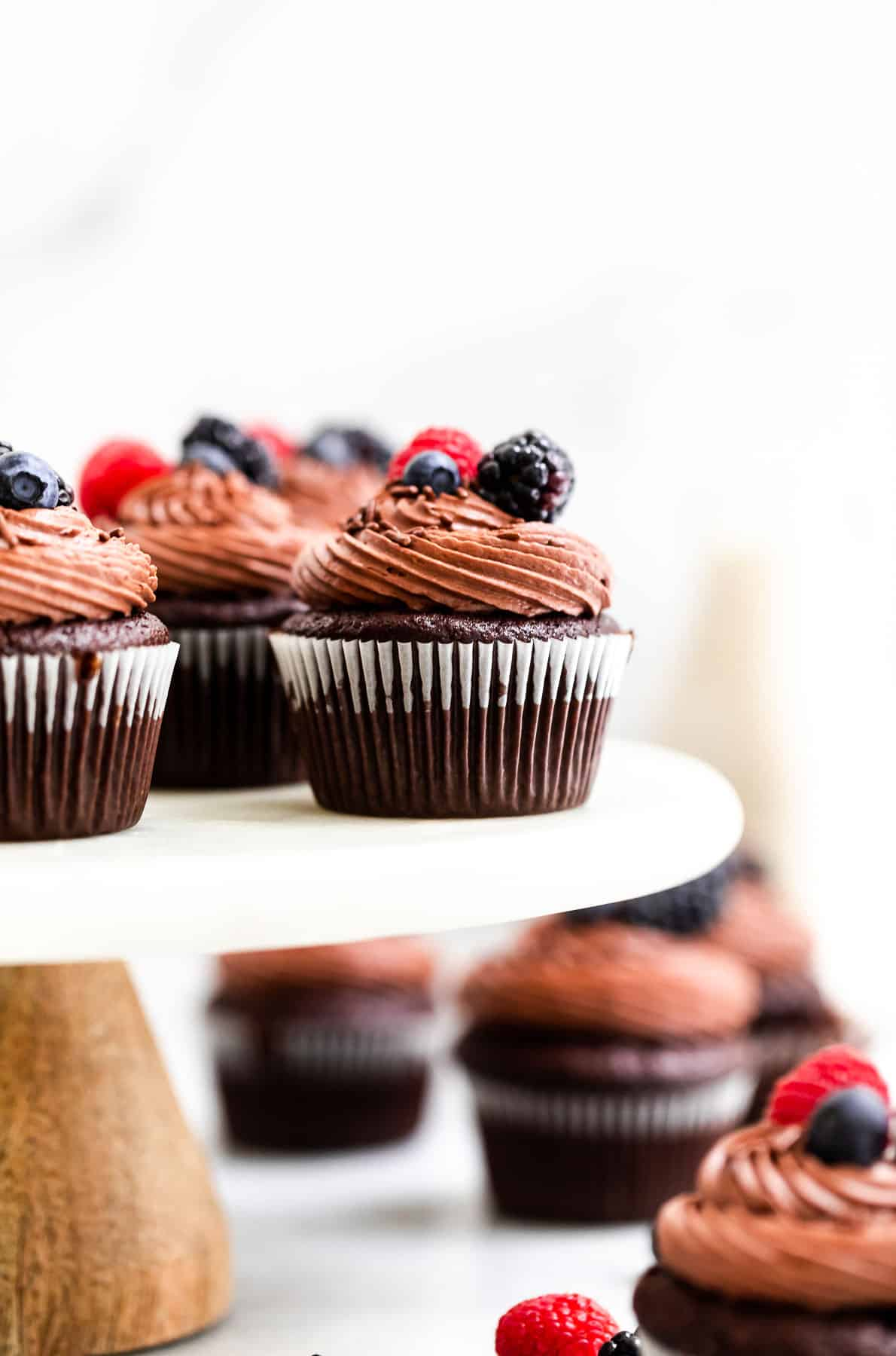 almond flour cupcakes on a cake stand with berries