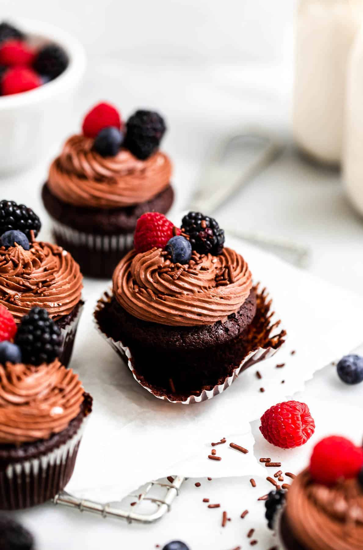 almond flour chocolate cupcakes with frosting and berries on top