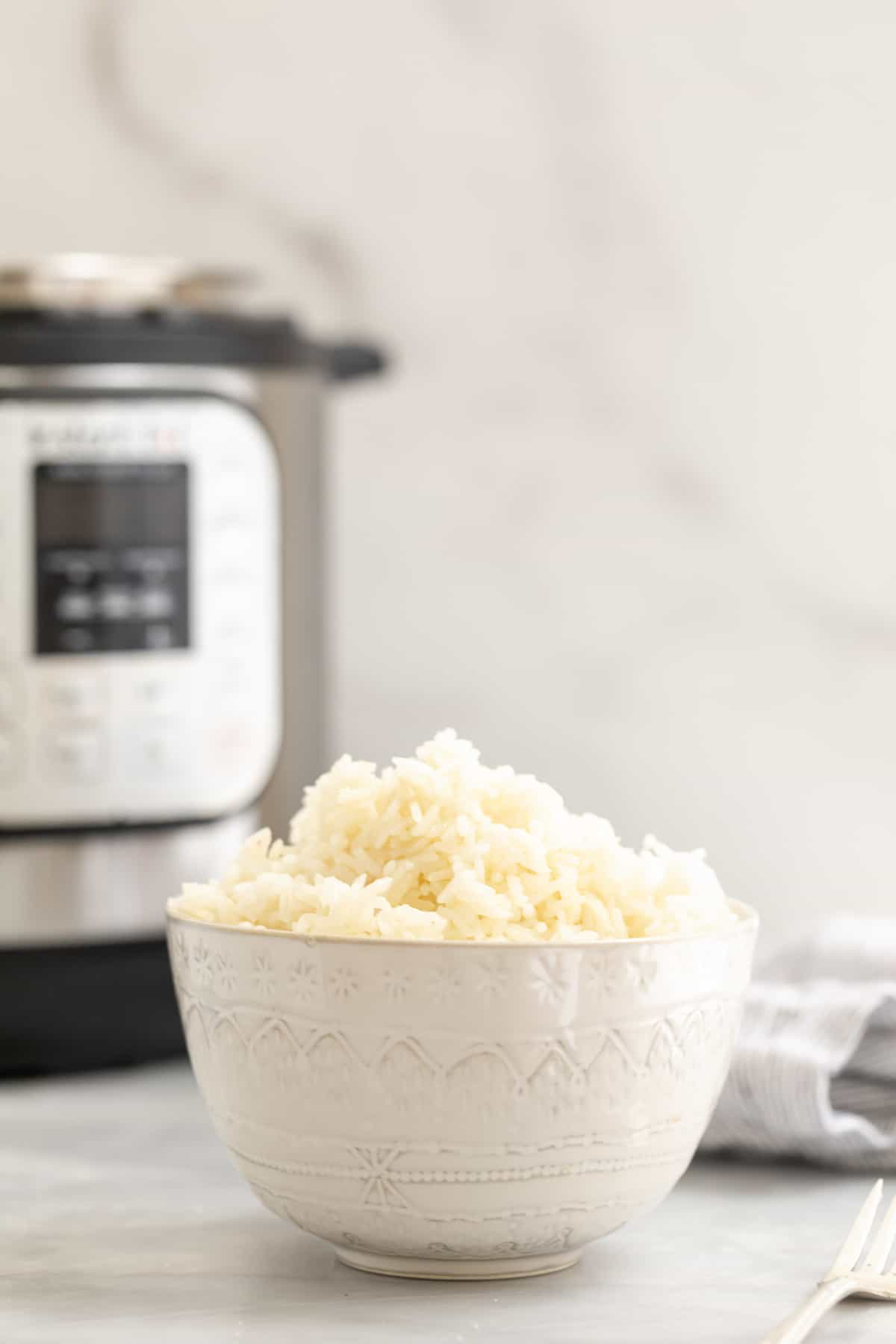 Bowl filled with white jasmine rice with the instant pot in the background.