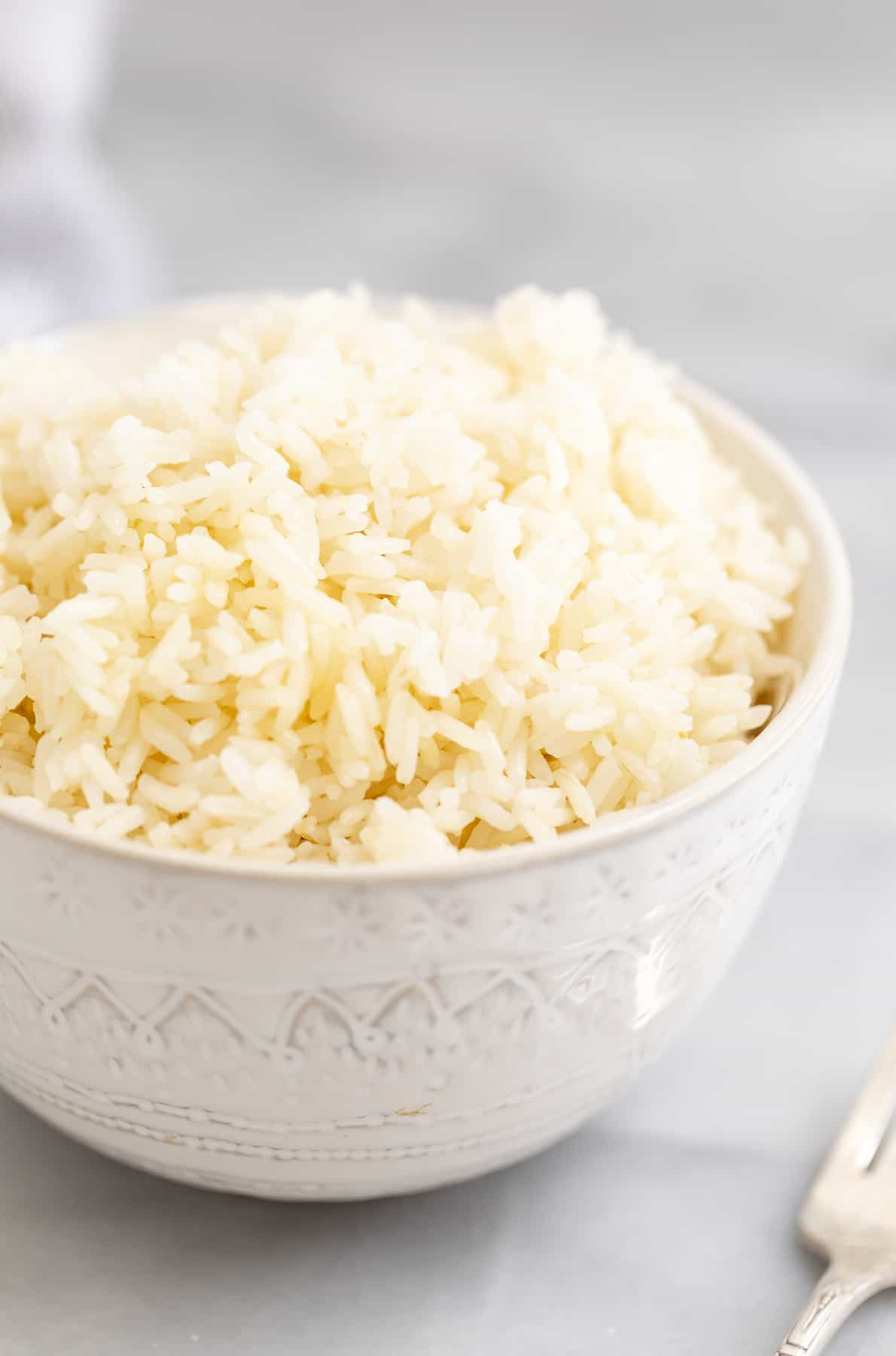Small white bowl filled with jasmine rice.