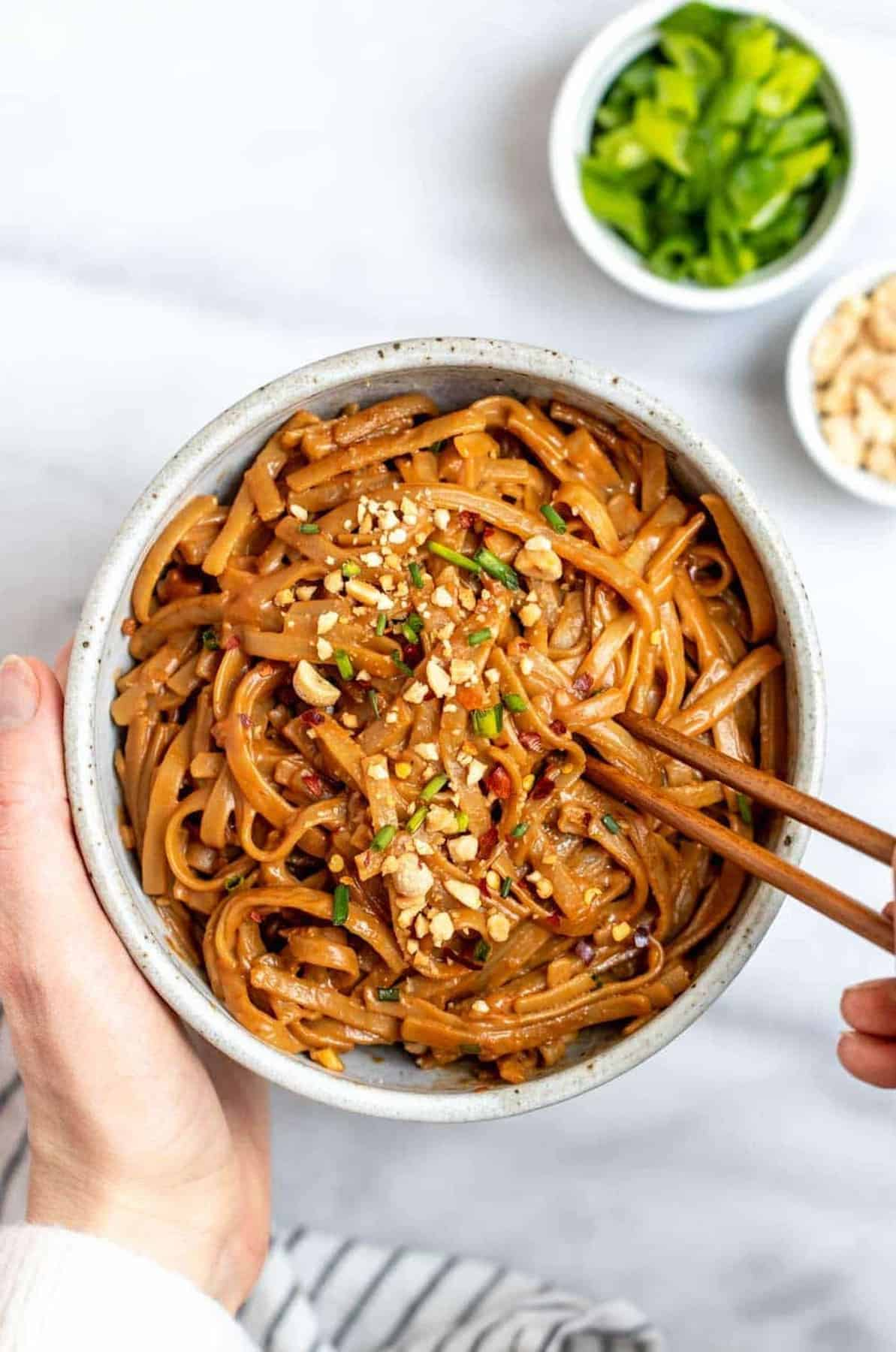 Hands holding a bowl with peanut butter noodles.