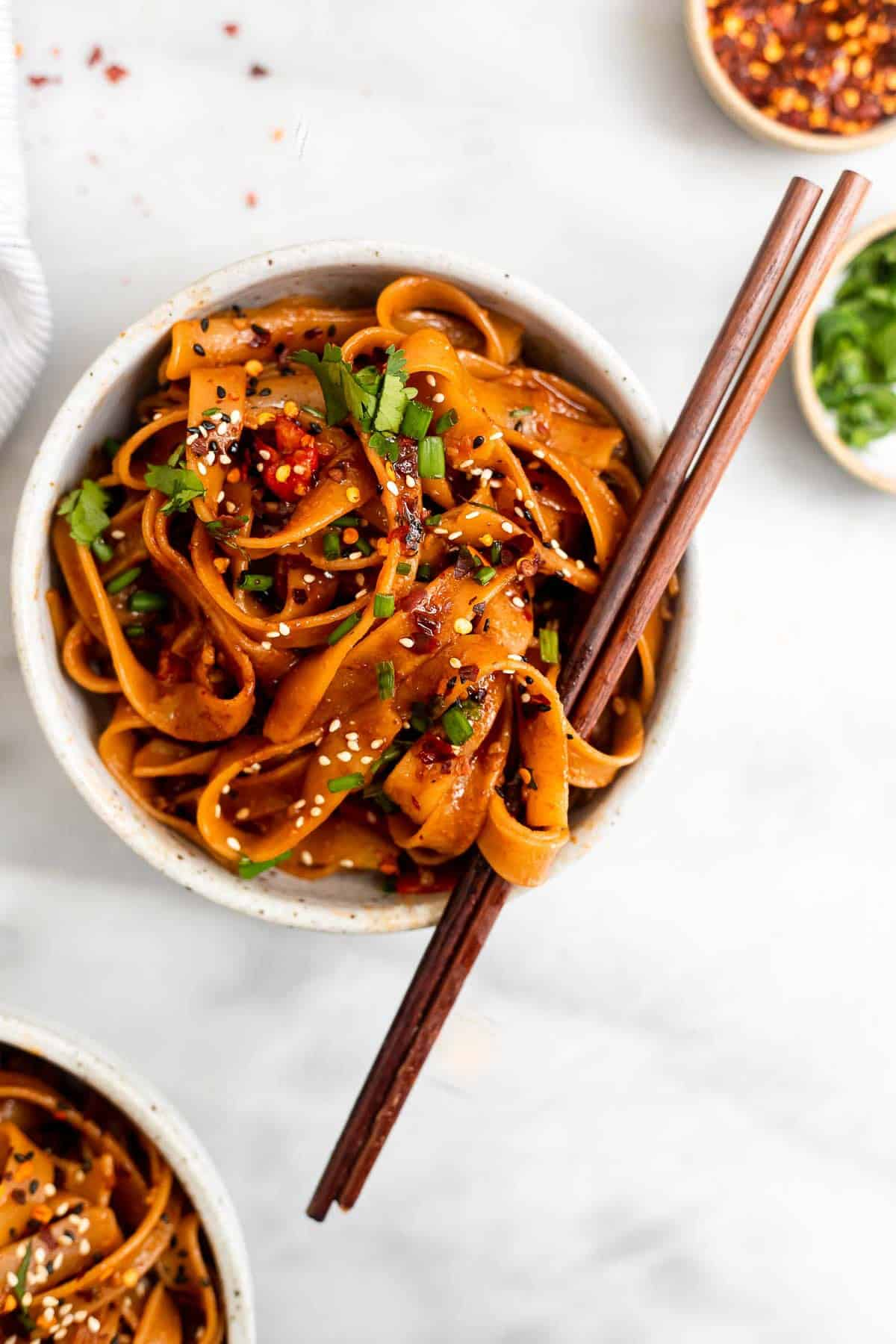 spicy noodles with chopsticks wrapped around the noodles