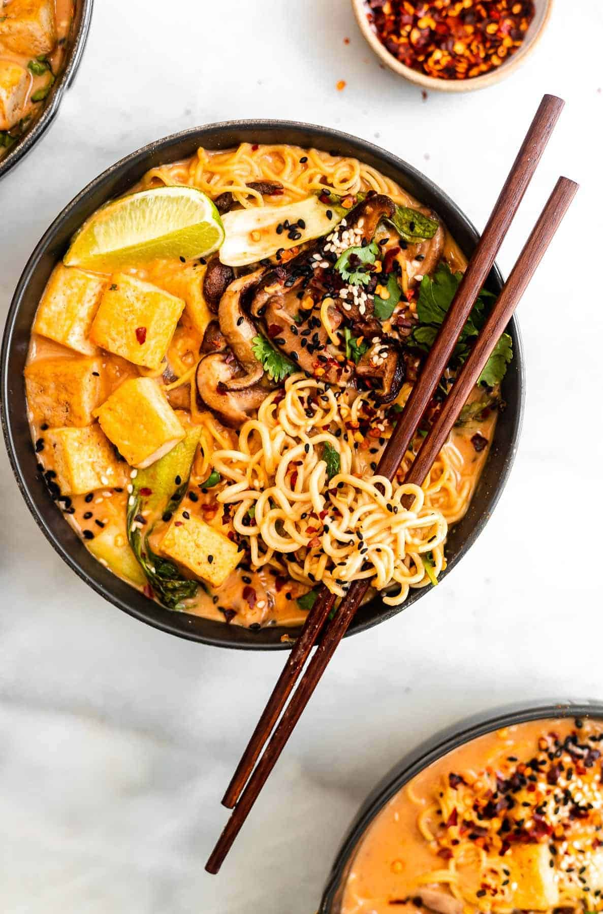 vegan curry ramen in a black bowl with noodles around the chopsticks