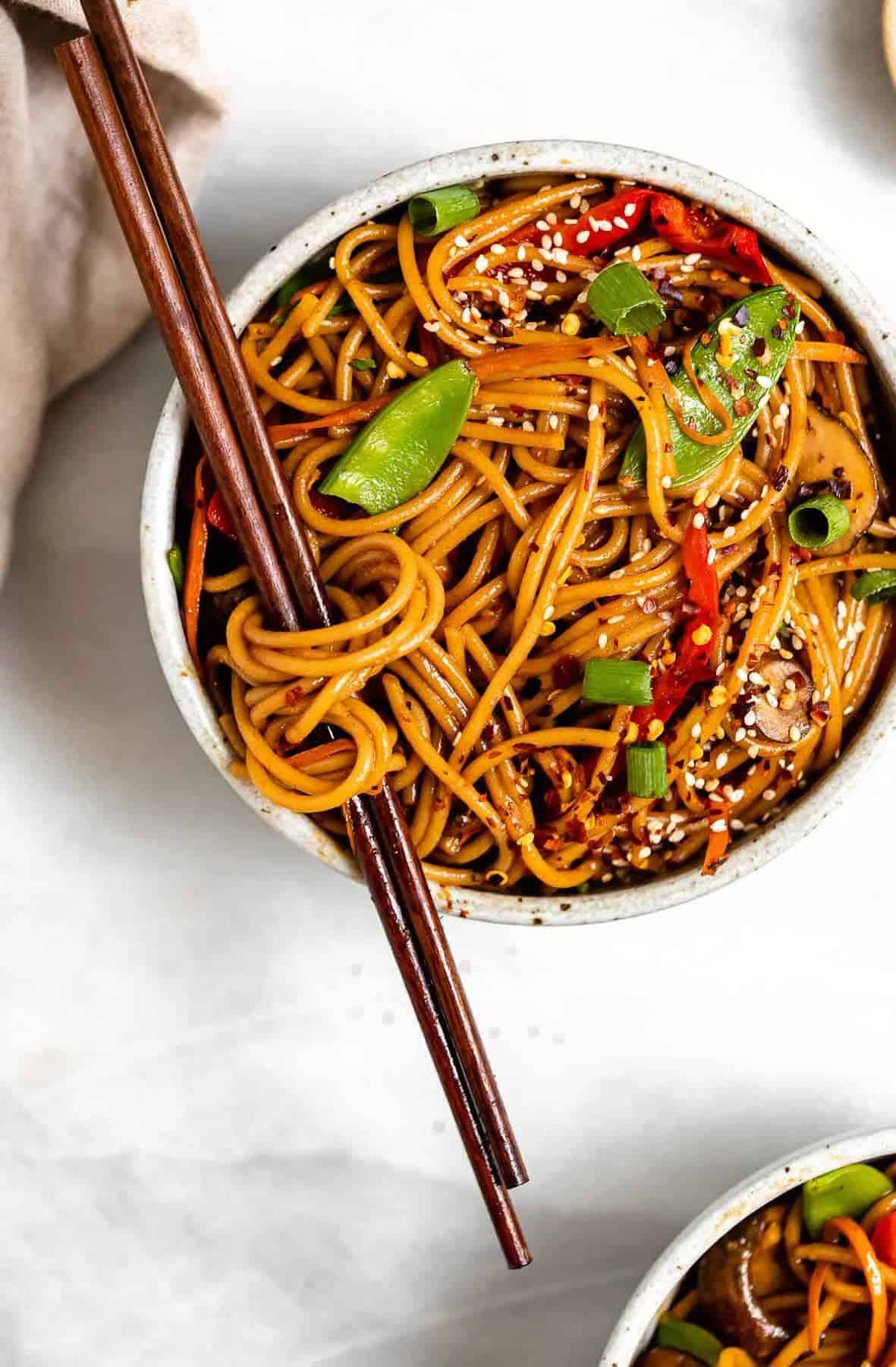 vegetable lo mein in a bowl with noodles wrapped around the chopsticks.