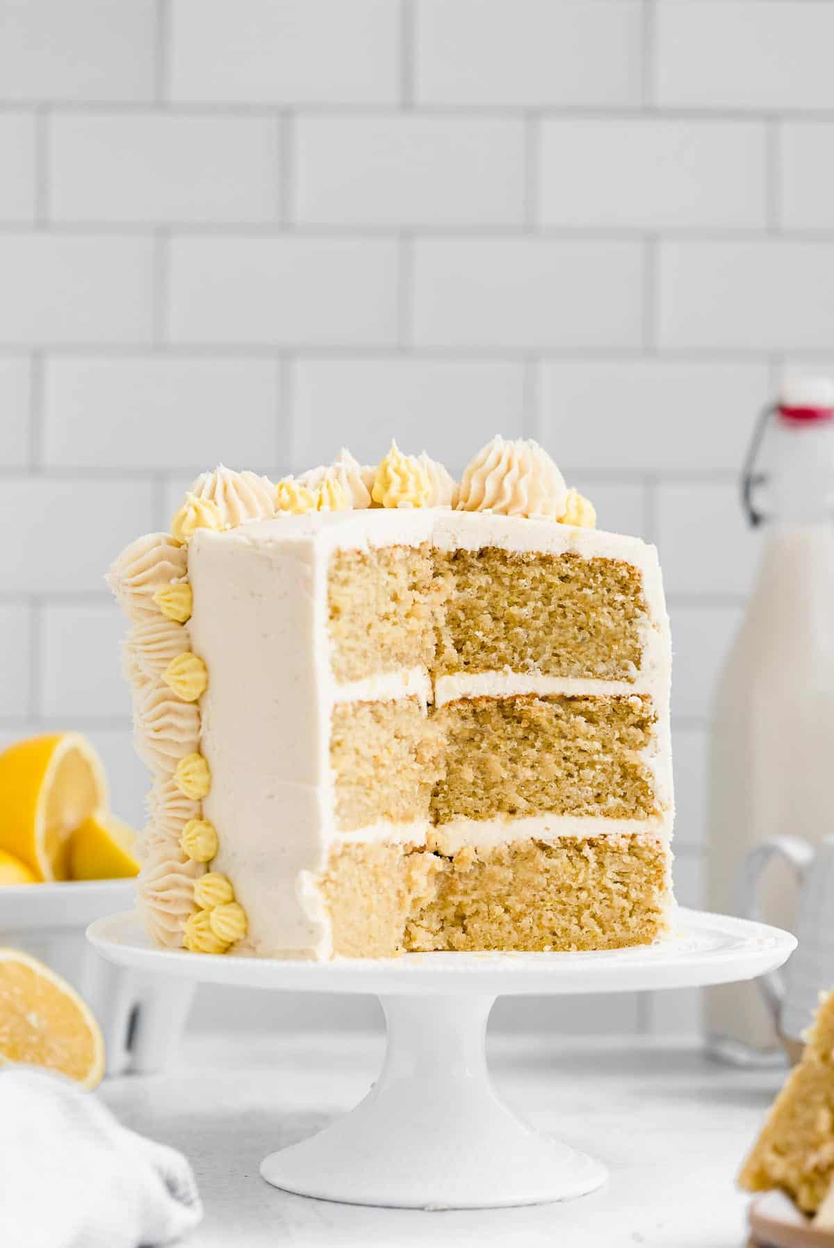 three layer lemon cake on a cake stand with lemon slices