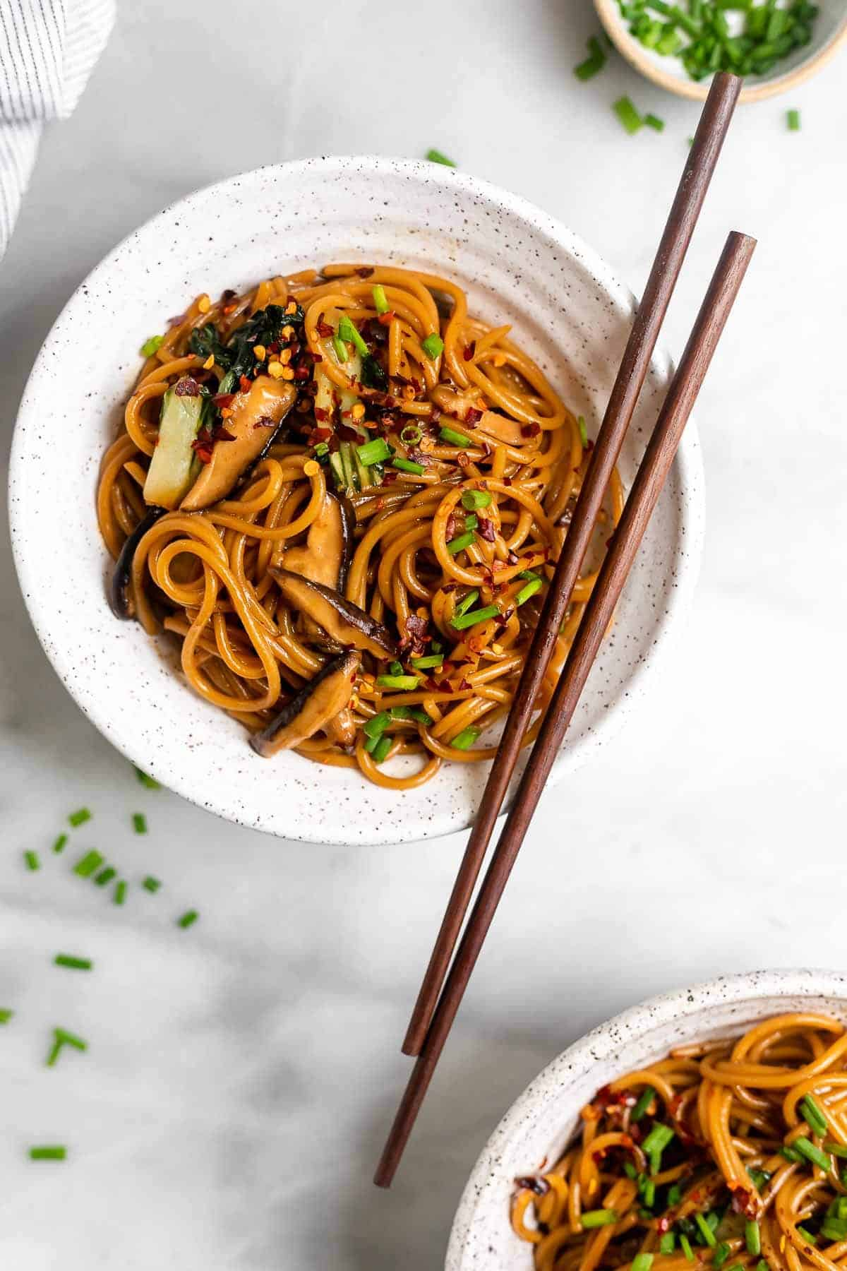 teriyaki noodles in a bowl with chopsticks on the side