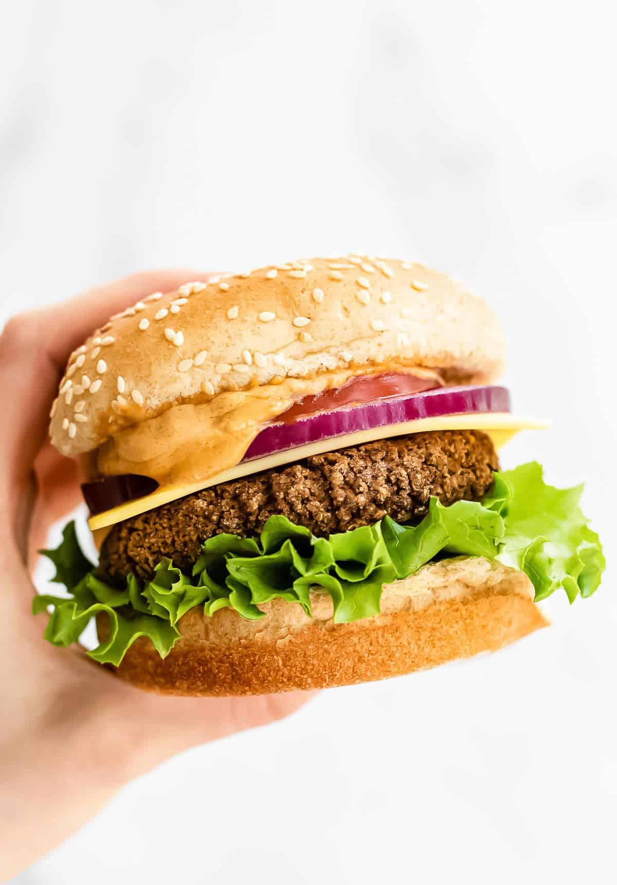 hands holding up a black bean burger with a sesame bun