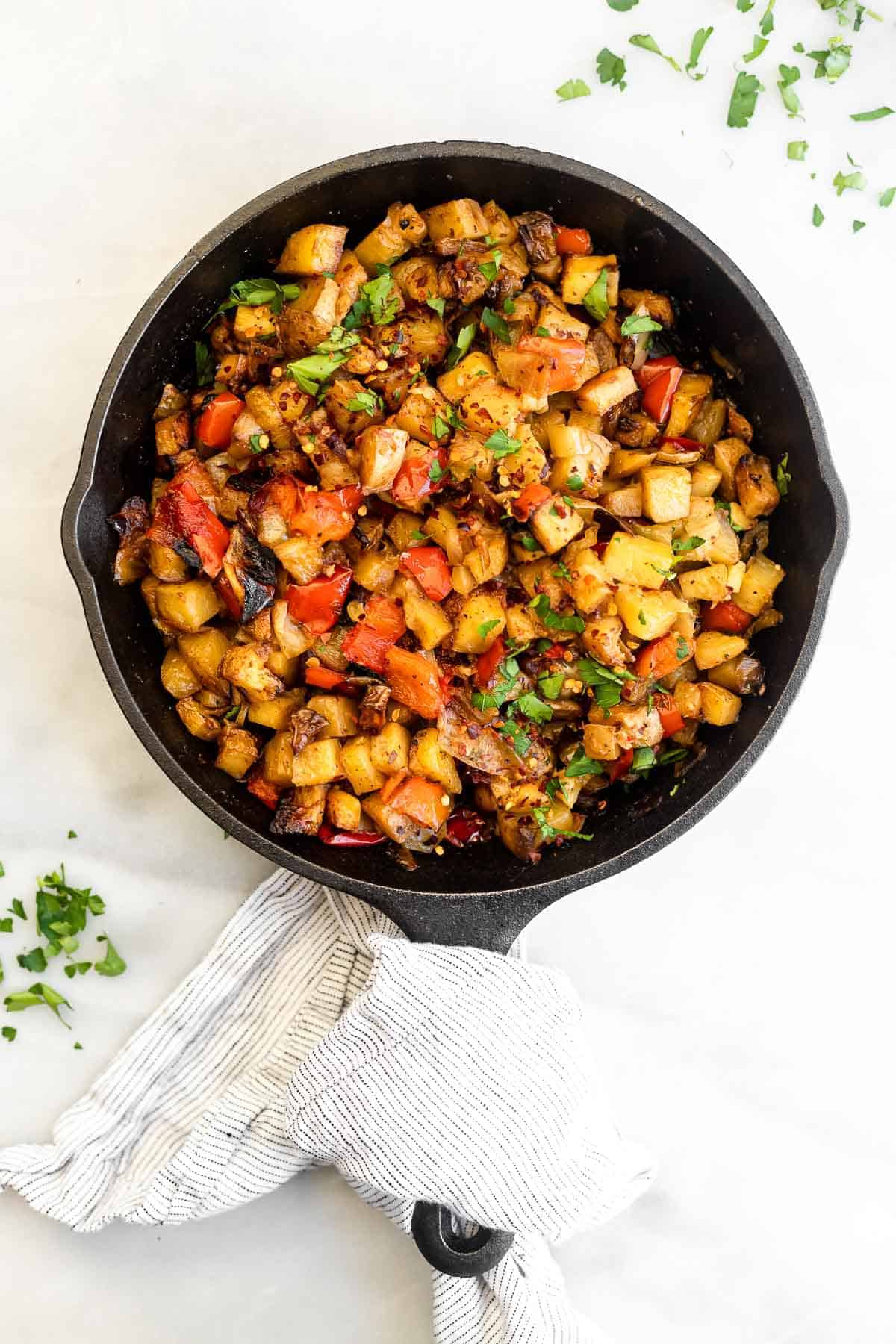 vegan breakfast potatoes in a black skillet with cilantro