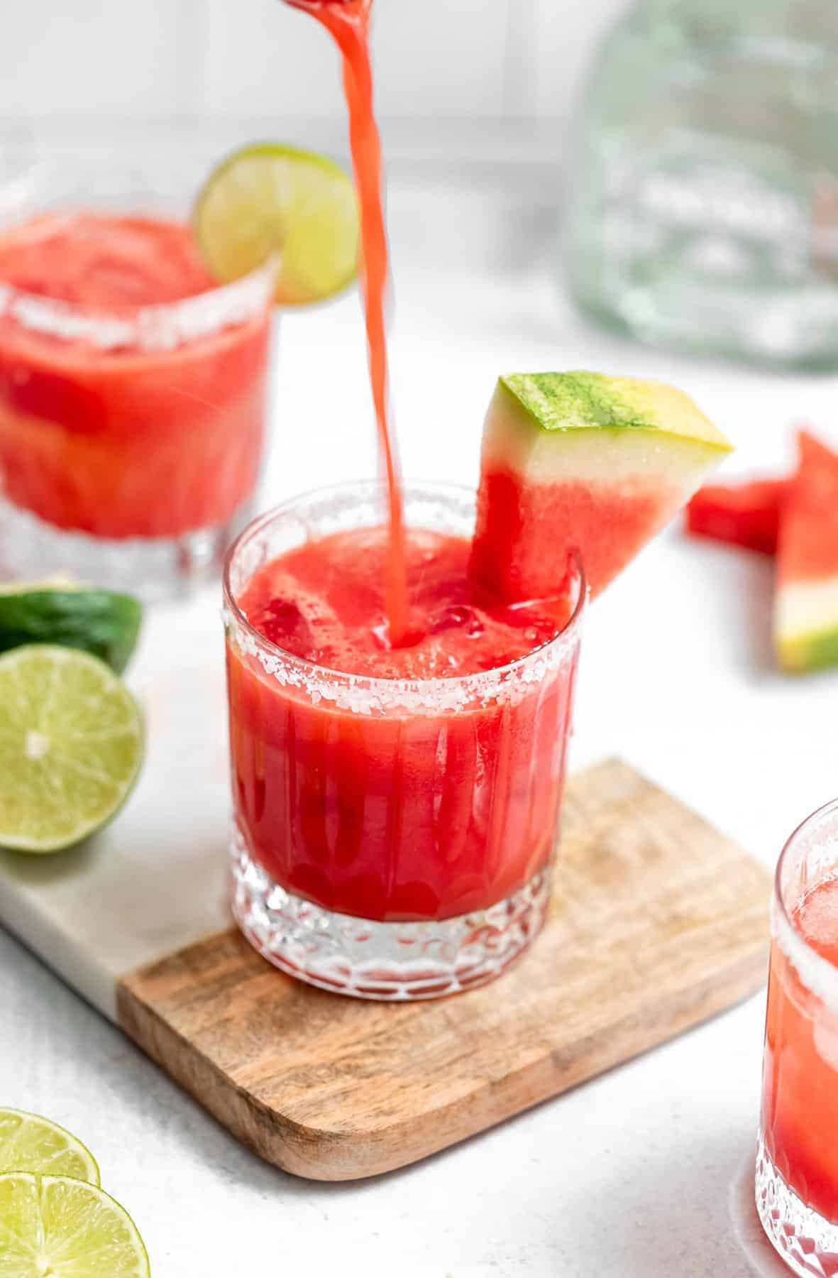 pouring the watermelon margarita into glasses