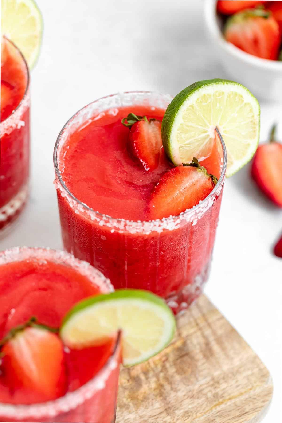 three frozen strawberry margaritas in a glass