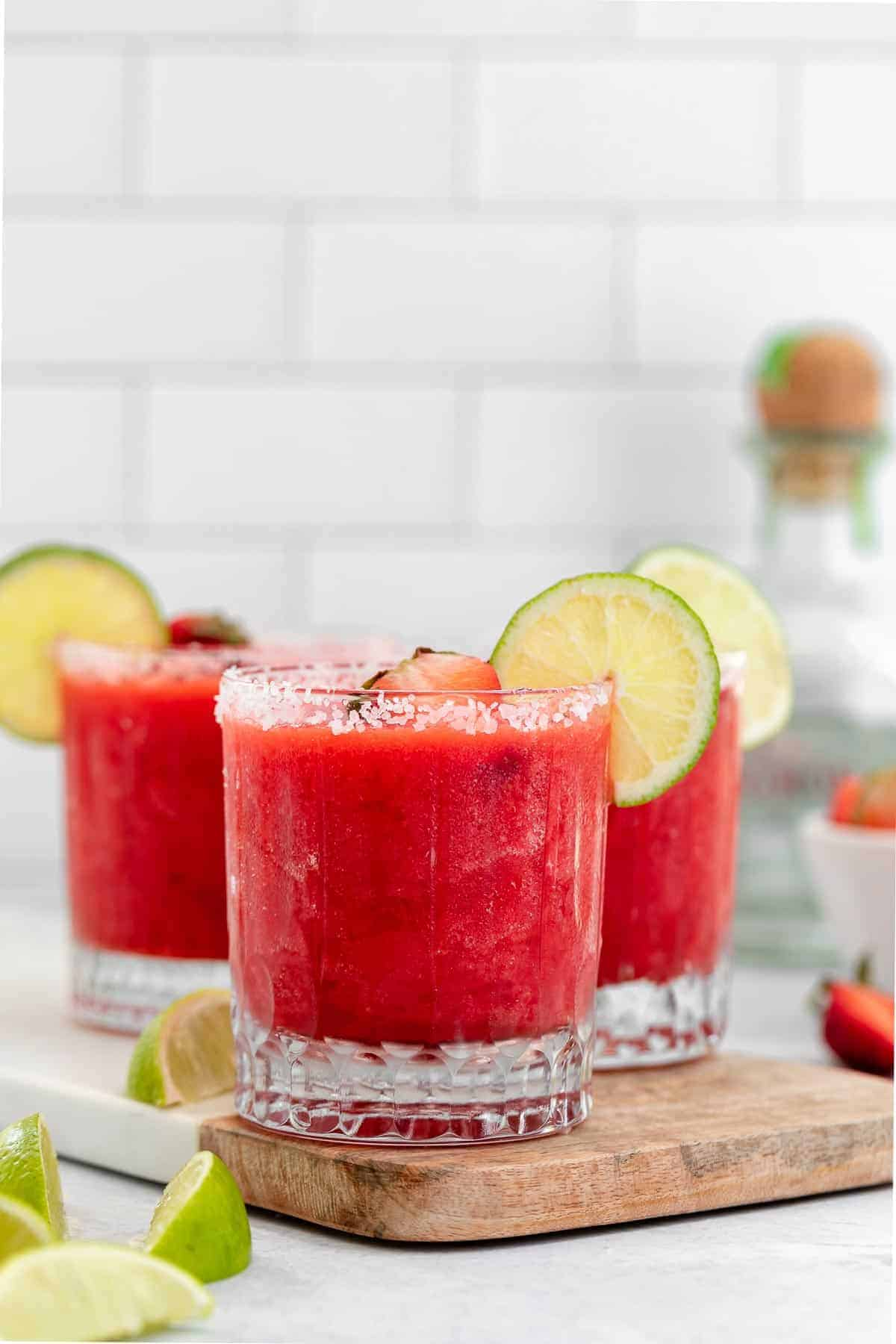 strawberry margarita in three glasses with lime wedges