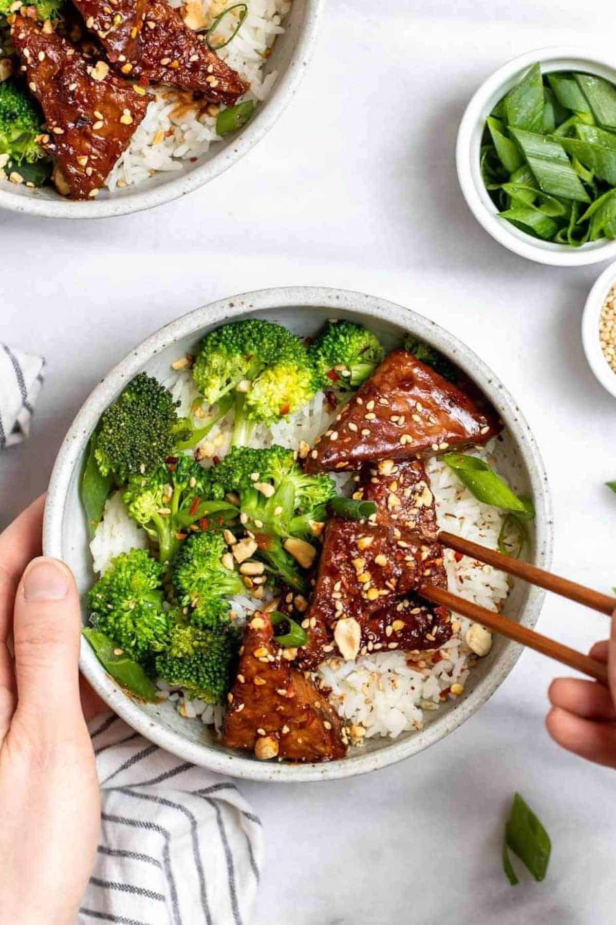 Marinated sesame peanut tempeh with broccoli and rice in a round bowl.