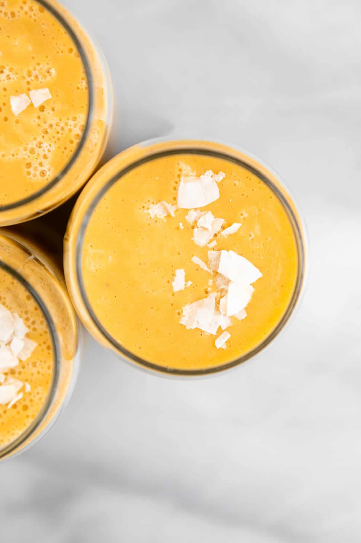 orange cantaloupe smoothie in three glasses with coconut on top