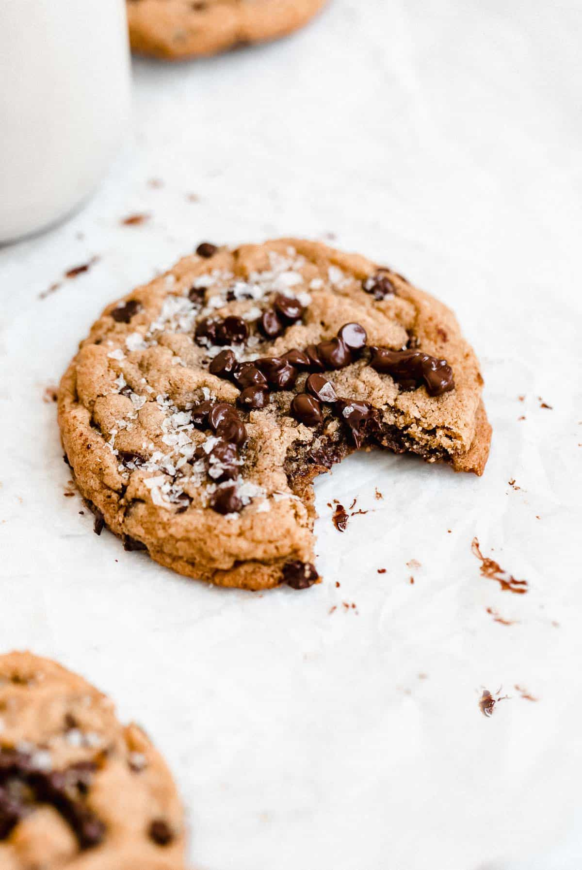 one cookie with a bite taken out on parchment paper