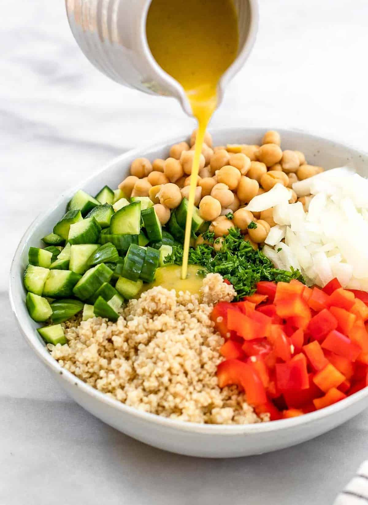 Pouring the dressing onto the quinoa tabbouleh salad.