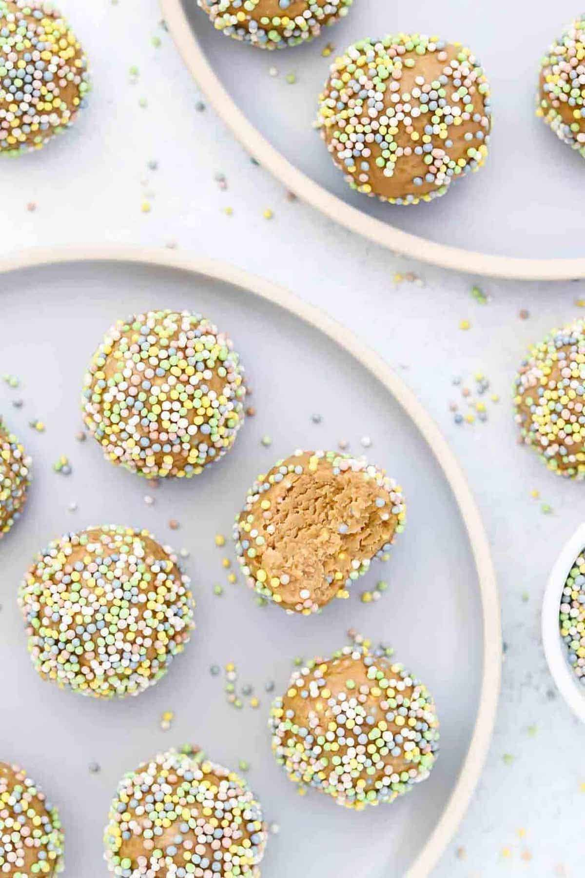 Bliss Balls on two blue plates with sprinkles.