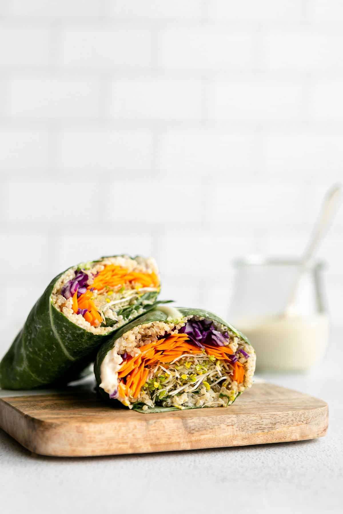 two collard wraps cut in half with quinoa and veggies